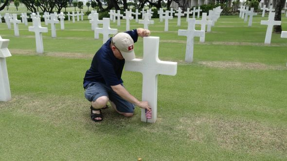 Planting a flag at the grave of a Citadel Man at Manila American Cemetery